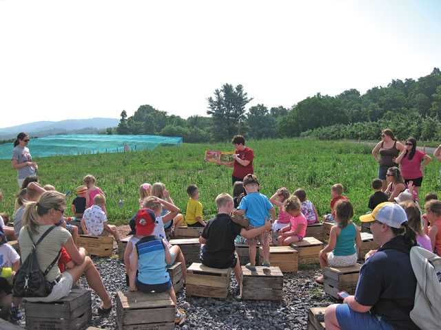 "Young children enrolled in the ""Read, Learn, Grow"" summer program at Hollabaugh Bros. Inc., listen to a story focused on fruits or vegetables. Fruit or vegetable picking or a craft activity are also part of the programming. (Photo credit: Photo credit: Hollabaugh Bros. Inc.)"