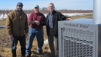 Michigan State University (MSU) Clarksville Research Center assistant farm manager Dan Platte (left) and MSU Department of Horticulture professor Gregory Lang (right) thank Lee DeLeeuw of Superior Wind Machine Service, Inc., for the donation of a wind machine to prevent frost damage to fruit research plots at the MSU AgBioResearch facility. (Photo credit: MSU AgBioResearch)