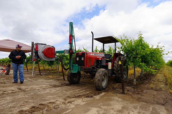 S. Kaan Kurtural discusses the use of a mechanical leafing machine for wine grape canopy management. (Photo credit: Matthew Fidelibus)