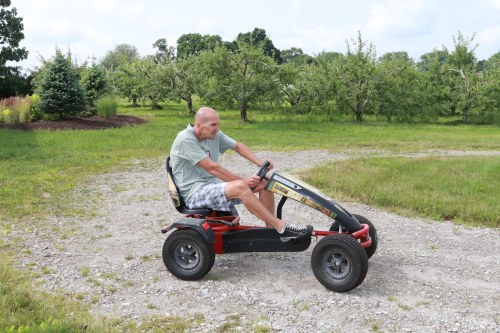 Hillcrest Orchards offers pedal karts, corn maze, and U-pick produce. Here, Bill Dodd poses on the kart track. (Photo credit: Maggie Puskas)