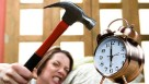 woman smashing an alarm clock with a hammer