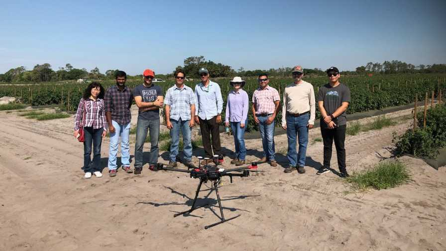 UF/IFAS researcher stand behind a drone outfitted with a special camera that can detect laurel wilt disease