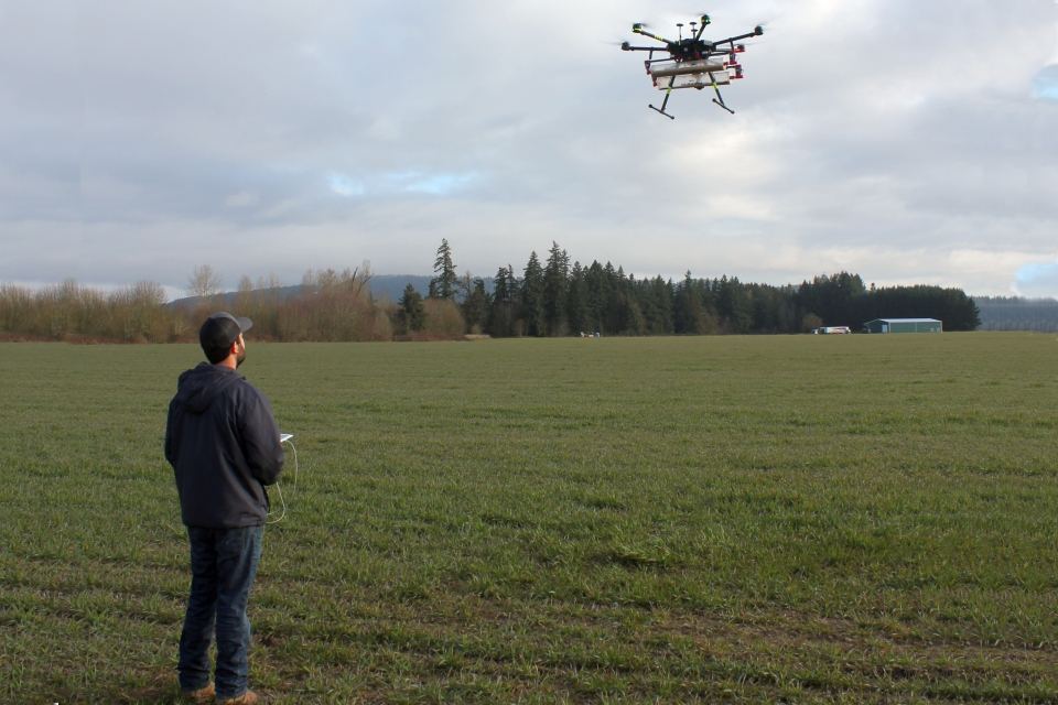 A grower flies the Parabug BCA carrying drone payload over a field as part of a field tour demonstration during the Biocontrols USA West 2019 Conference & Expo in Portland, OR.