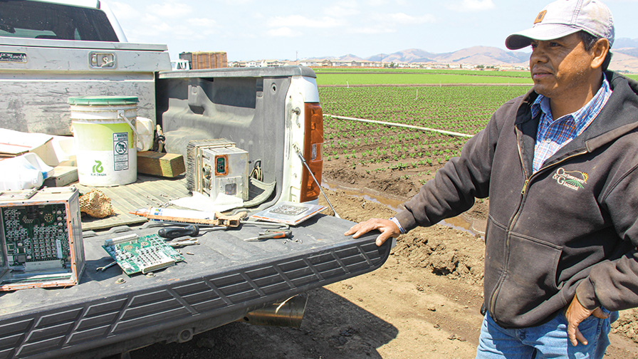 feature_Farm worker with computer modules and tech in truck