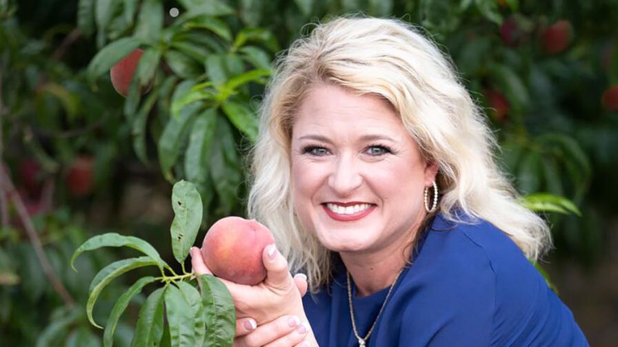 Lori Anne Carr of Titan Farms holding the 'Lori Anne' peach